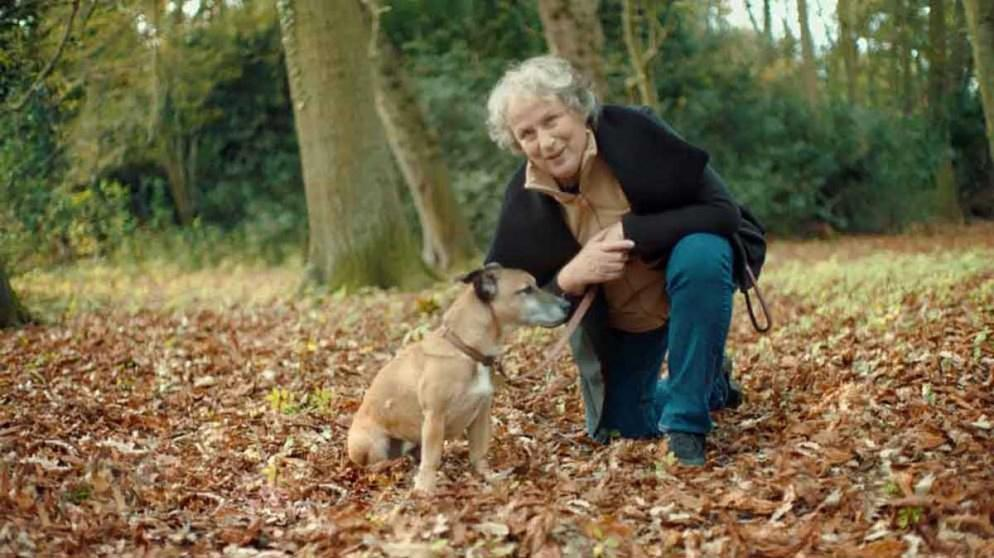Pam Ferris with dog in autumnal forest