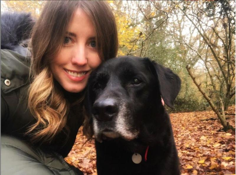 Woman posing for a selfie with her dog, a black Labrador