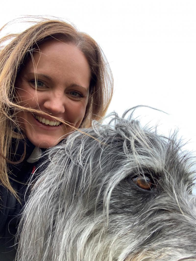 Woman laughing looking into camera with her lurcher in front of her